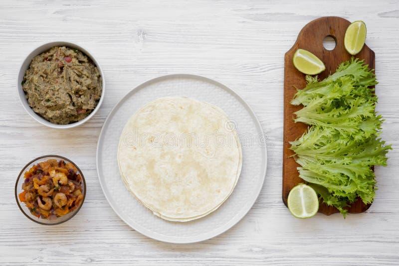 Συστατικά taco γαρίδων στο άσπρο ξύλινο υπόβαθρο, τοπ άποψη Επίπεδος βάλτε, γενικά έξοδα στοκ φωτογραφία με δικαίωμα ελεύθερης χρήσης