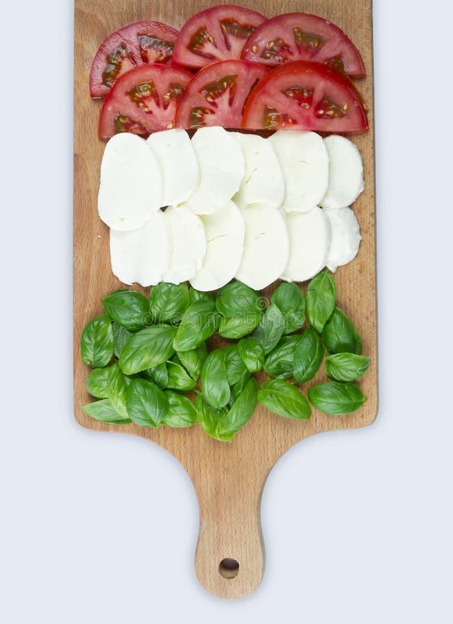 Συστατικό για τη σαλάτα Caprese Τεμαχισμένες ντομάτες, μοτσαρέλα και δέσμη του βασιλικού στοκ φωτογραφίες