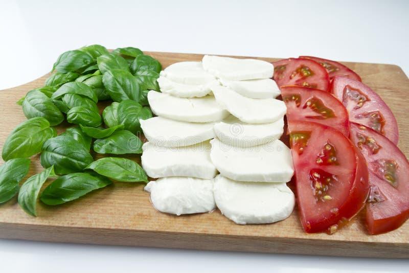 Συστατικό για τη σαλάτα Caprese Τεμαχισμένες ντομάτες, μοτσαρέλα και δέσμη του βασιλικού στοκ εικόνα με δικαίωμα ελεύθερης χρήσης