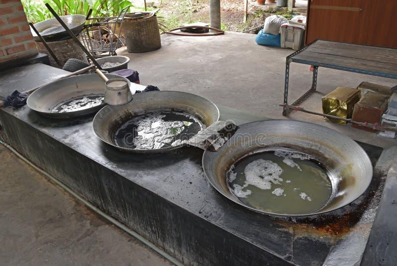 Συλλεχθε'ν σφρίγος δέντρων καρύδων από στα μεγάλα woks για να εξατμίσει την περιεκτικότητα σε υγρασία του σφρίγους στοκ εικόνες