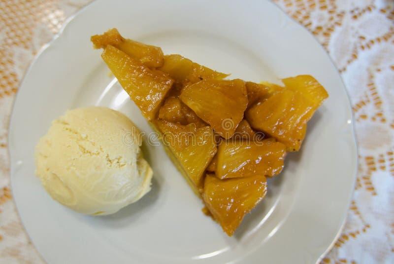 Σφήνα της άνω πλευράς ανανά - κάτω από το κέικ σε ένα άσπρο πιάτο με μια σέσουλα του παγωτού στην πλευρά στοκ φωτογραφία με δικαίωμα ελεύθερης χρήσης