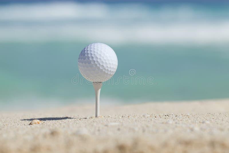Σφαίρα γκολφ στο γράμμα Τ στην παραλία άμμου με τα ωκεάνια κύματα πίσω στοκ φωτογραφία με δικαίωμα ελεύθερης χρήσης