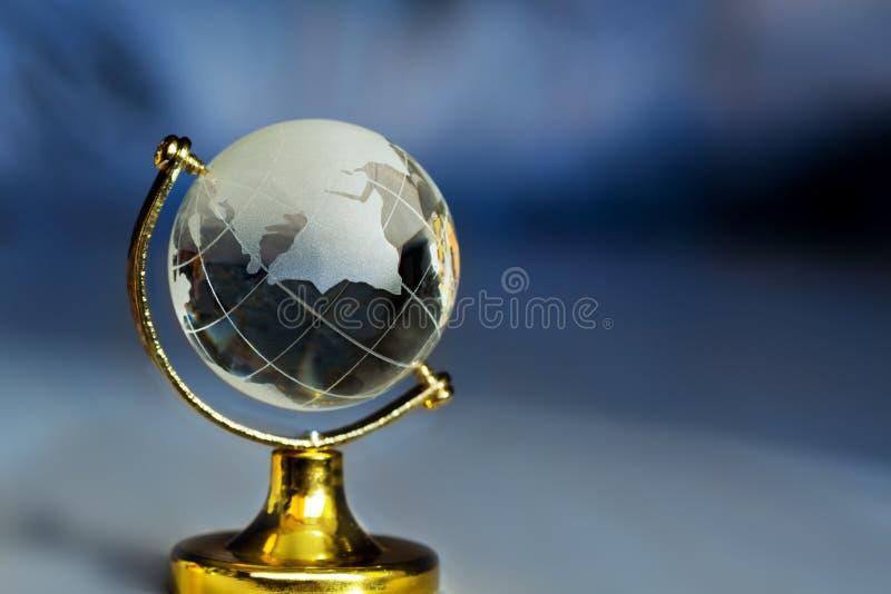 Σφαίρα γυαλιού σε μια στάση σε ένα μπλε υπόβαθρο με τις ακτίνες Σφαίρα πλανήτη Γη με το ειδώλιο ηπείρων στον πίνακα στοκ εικόνες
