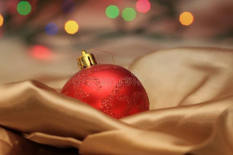 Σφαίρα γυαλιού Χριστουγέννων που βρίσκεται στο χρυσό μετάξι στοκ φωτογραφία