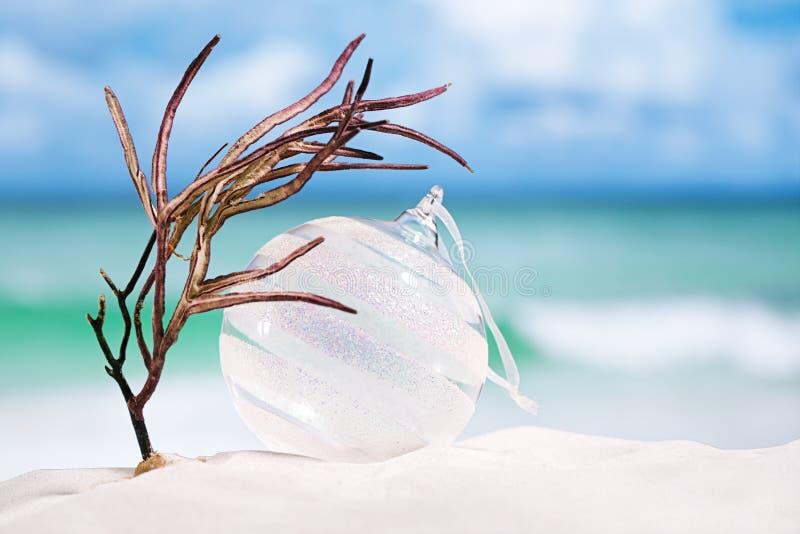 Σφαίρα γυαλιού Χριστουγέννων στην άσπρη παραλία άμμου με seascape το backgrou στοκ εικόνα