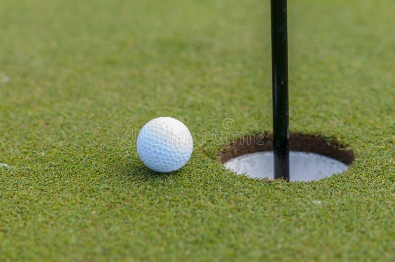 Σφαίρα και τρύπα γκολφ στοκ φωτογραφίες