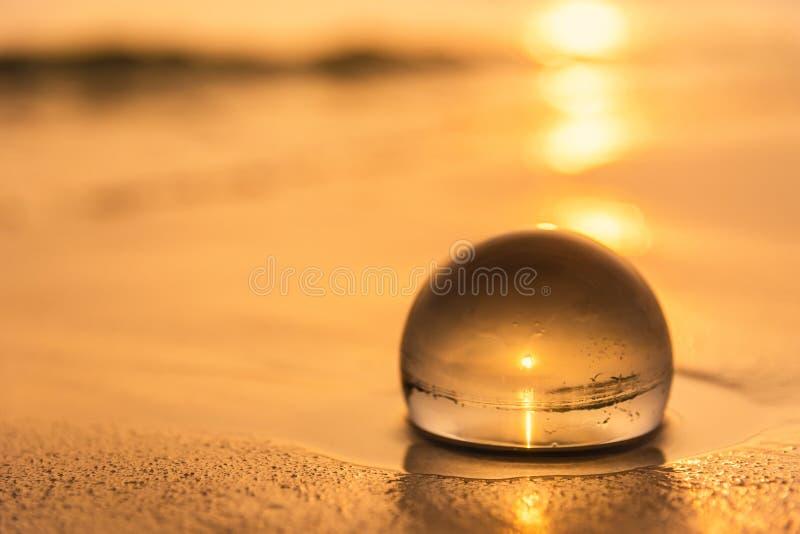 Σφαίρα κρυστάλλου στην παραλία με τα κύματα θάλασσας στην ανατολή πρωινού Ταϊλάνδη στοκ εικόνες