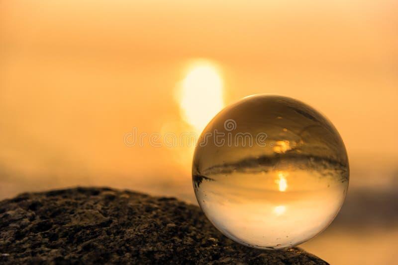 Σφαίρα κρυστάλλου στην παραλία με τα κύματα θάλασσας στην ανατολή πρωινού Ταϊλάνδη στοκ εικόνα