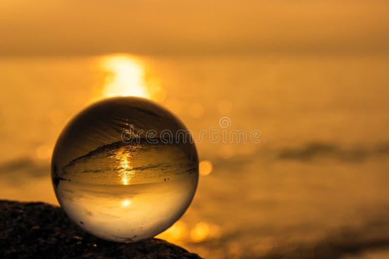 Σφαίρα κρυστάλλου στην παραλία με τα κύματα θάλασσας στην ανατολή πρωινού Ταϊλάνδη στοκ φωτογραφία