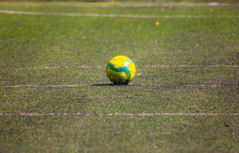 Σφαίρα με τα χρώματα της Βραζιλίας στη μέση ενός συνθετικού γηπέδου ποδοσφαίρου με 5 στοκ εικόνα με δικαίωμα ελεύθερης χρήσης