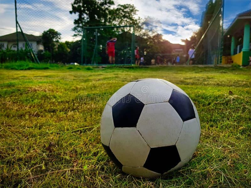 Σφαίρα ποδοσφαίρου κινηματογραφήσεων σε πρώτο πλάνο στον τομέα με τους ανθρώπους που παίζουν το ποδόσφαιρο σε απόμακρο στοκ φωτογραφίες