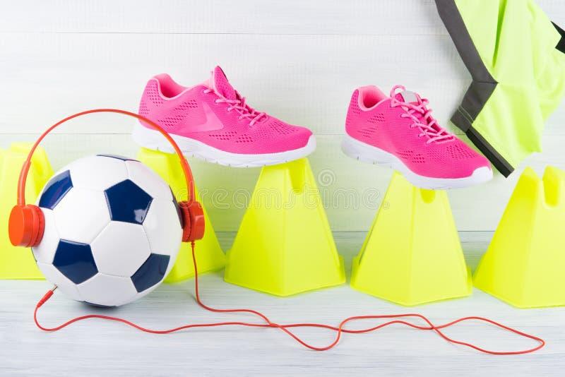 Σφαίρα ποδοσφαίρου με τα κόκκινα ακουστικά, ανάμεσα σε μια σειρά των κίτρινων κώνων και των ρόδινων πάνινων παπουτσιών, σε ένα γκ στοκ εικόνες