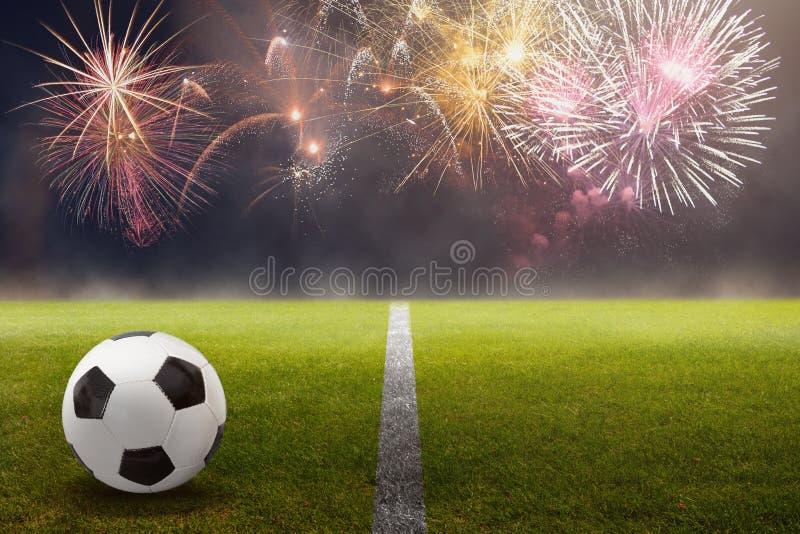 Σφαίρα ποδοσφαίρου στο πράσινο ενάντια στα όμορφα πυροτεχνήματα στοκ εικόνες