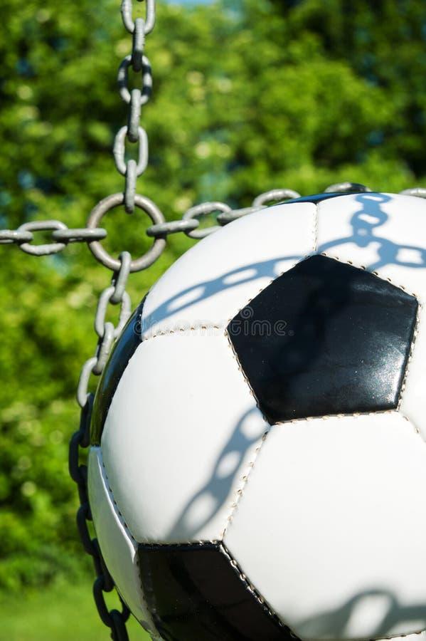 Σφαίρα ποδοσφαίρου στο στόχο με τις αλυσίδες και στενό επάνω φυσικού υποβάθρου στοκ εικόνες με δικαίωμα ελεύθερης χρήσης