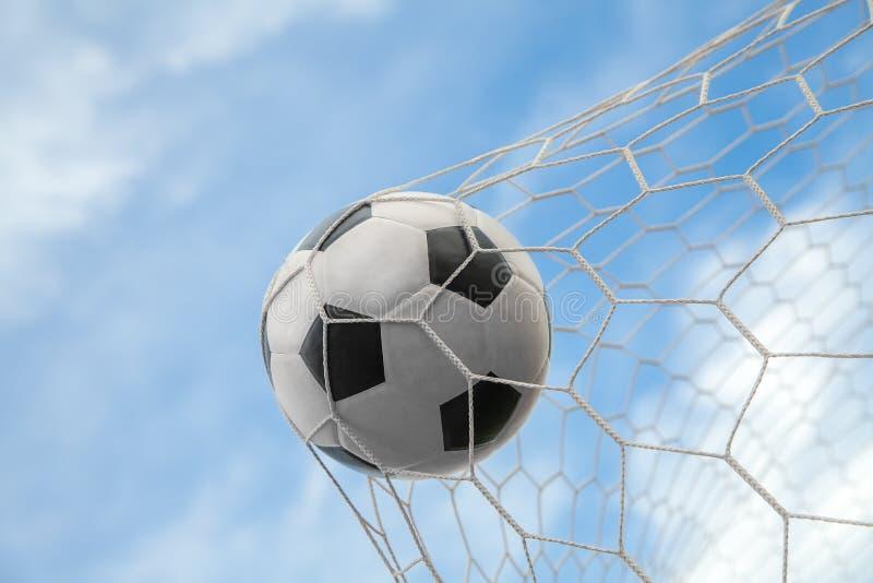 Σφαίρα ποδοσφαίρου στο στόχο με το καθαρό και υπόβαθρο ουρανού στοκ εικόνες