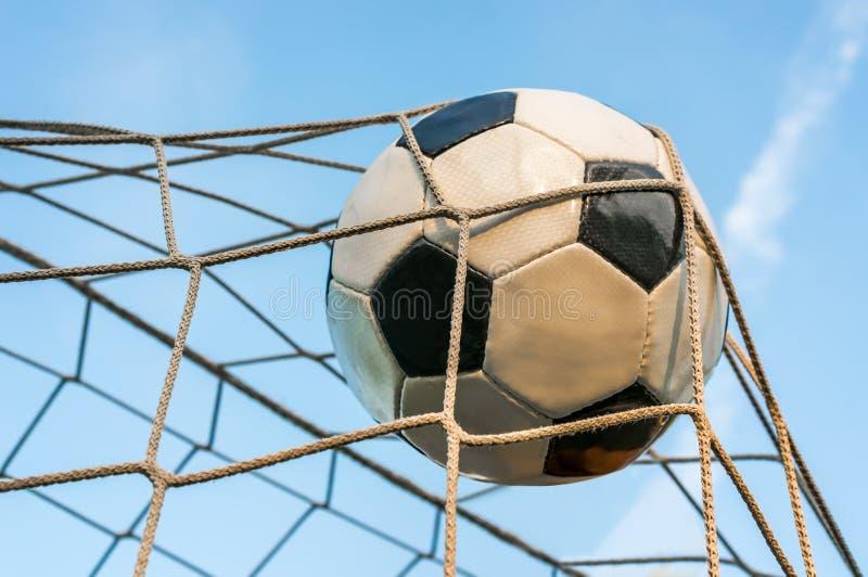 Σφαίρα ποδοσφαίρου στο στόχο καθαρό με το υπόβαθρο μπλε ουρανού στοκ εικόνα