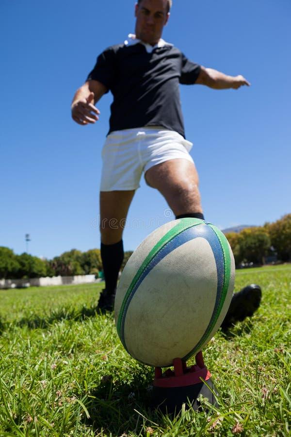 Σφαίρα ράγκμπι λακτίσματος φορέων στο χλοώδη τομέα στοκ φωτογραφίες με δικαίωμα ελεύθερης χρήσης