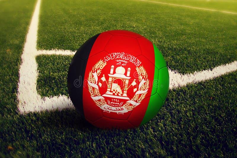 Σφαίρα του Αφγανιστάν στη θέση λακτίσματος γωνιών, υπόβαθρο γηπέδων ποδοσφαίρου Εθνικό θέμα ποδοσφαίρου στην πράσινη χλόη στοκ εικόνες με δικαίωμα ελεύθερης χρήσης