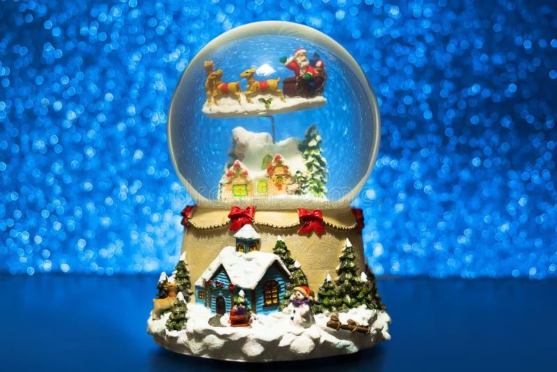 Σφαίρα χιονιού Χριστουγέννων με snowflake Το αναμνηστικό γυαλιού του νέου έτους σε μπλε που θολώνεται ακτινοβολεί υπόβαθρο φω'των στοκ φωτογραφία