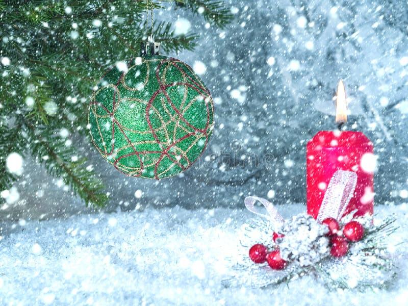 Σφαίρα Χριστουγέννων σε έναν κλάδο και ένα καίγοντας κερί κάτω από ένα μειωμένο χιόνι στοκ φωτογραφία με δικαίωμα ελεύθερης χρήσης