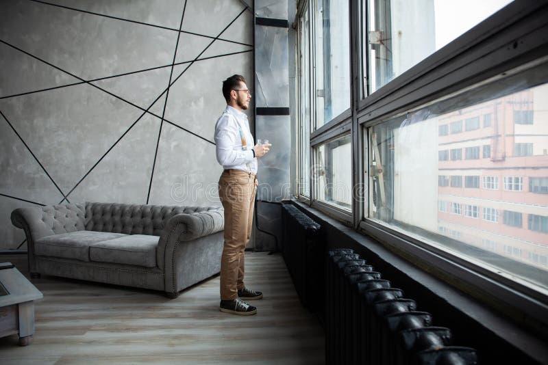 σφαίρες διαστατικά τρία Το μοντέρνο νέο γενειοφόρο άτομο στέκεται κοντά στο παράθυρο και κοιτάζει μακριά Είναι σε ένα κοστούμι, σ στοκ εικόνα με δικαίωμα ελεύθερης χρήσης