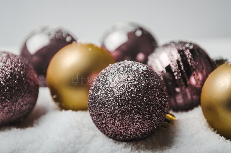 Σφαίρες σφαιρών Χριστουγέννων πορφυρός και χρυσός στο τεχνητό χιόνι στο άσπρο υπόβαθρο στοκ εικόνες με δικαίωμα ελεύθερης χρήσης
