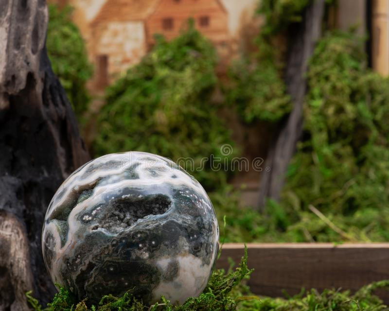 Σφαιρική ωκεάνια σφαίρα ιασπίδων με κρυσταλλωμένος vugs από τη Μαδαγασκάρη στο βρύο, το bryophyta και το ξύλο στοκ φωτογραφία με δικαίωμα ελεύθερης χρήσης