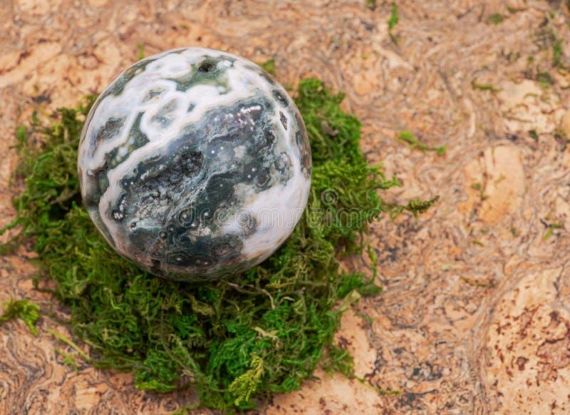 Σφαιρική ωκεάνια σφαίρα ιασπίδων με κρυσταλλωμένος vugs από τη Μαδαγασκάρη στο βρύο, το bryophyta και το φελλό στοκ εικόνες