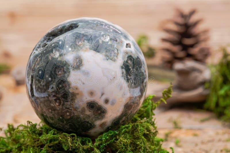 Σφαιρική ωκεάνια σφαίρα ιασπίδων με κρυσταλλωμένος vugs από τη Μαδαγασκάρη στο βρύο, το bryophyta και το φελλό στοκ φωτογραφία με δικαίωμα ελεύθερης χρήσης