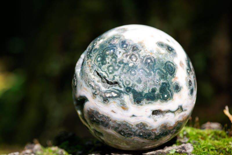 Σφαιρική ωκεάνια σφαίρα ιασπίδων με κρυσταλλωμένος vugs από τη Μαδαγασκάρη στο βρύο, το bryophyta και το φλοιό, rhytidome στο δάσ στοκ εικόνες