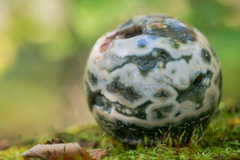 Σφαιρική ωκεάνια σφαίρα ιασπίδων με κρυσταλλωμένος vugs από τη Μαδαγασκάρη στο βρύο, το bryophyta και το φλοιό, rhytidome στο δάσ στοκ φωτογραφία
