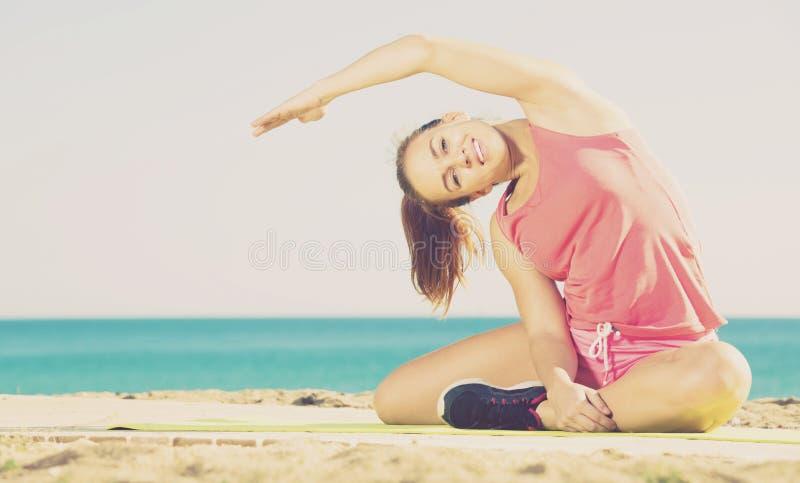 Σφριγηλή νέα γυναίκα που ασκεί στο χαλί άσκησης υπαίθριο στοκ φωτογραφία με δικαίωμα ελεύθερης χρήσης