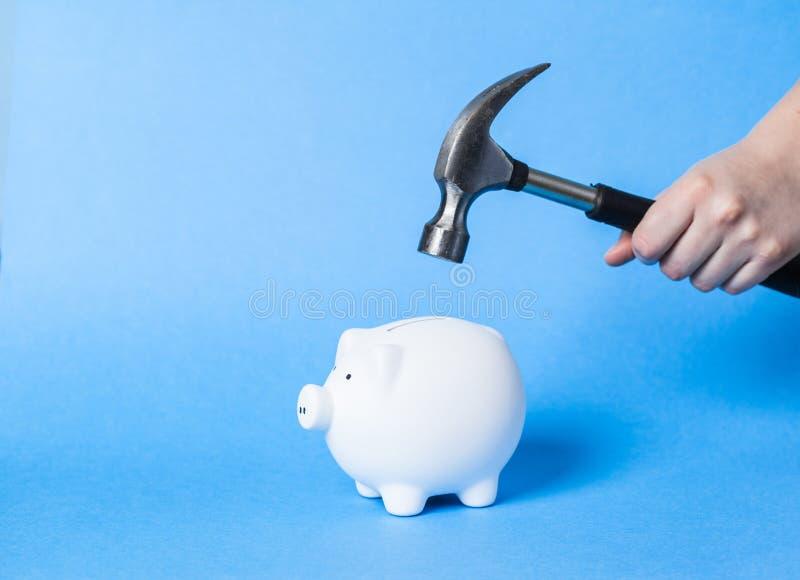 Σφυρί που αυξάνεται επάνω από μια άσπρη piggy τράπεζα στοκ εικόνα με δικαίωμα ελεύθερης χρήσης
