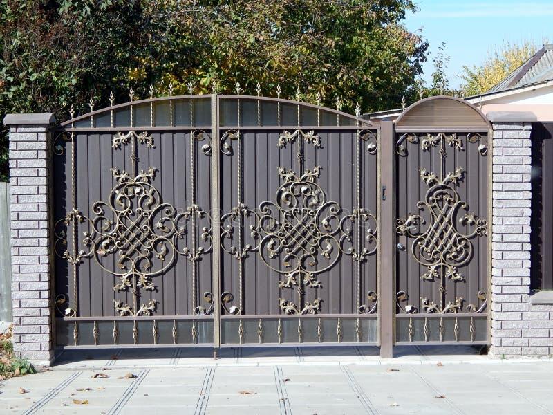 Σφυρηλατημένη μεταλλική πύλη με μια πύλη σε έναν φράκτη στοκ εικόνα