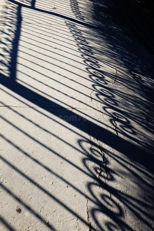 Σφυρηλατημένη σκιά φρακτών σε μια διαδρομή στοκ εικόνες με δικαίωμα ελεύθερης χρήσης