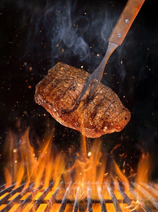 Σχάρα κατσαρολών με τις καυτές ανθρακόπλινθους, τη σχάρα χυτοσιδήρου και τις νόστιμες μπριζόλες βόειου κρέατος που πετούν στον αέ στοκ φωτογραφία