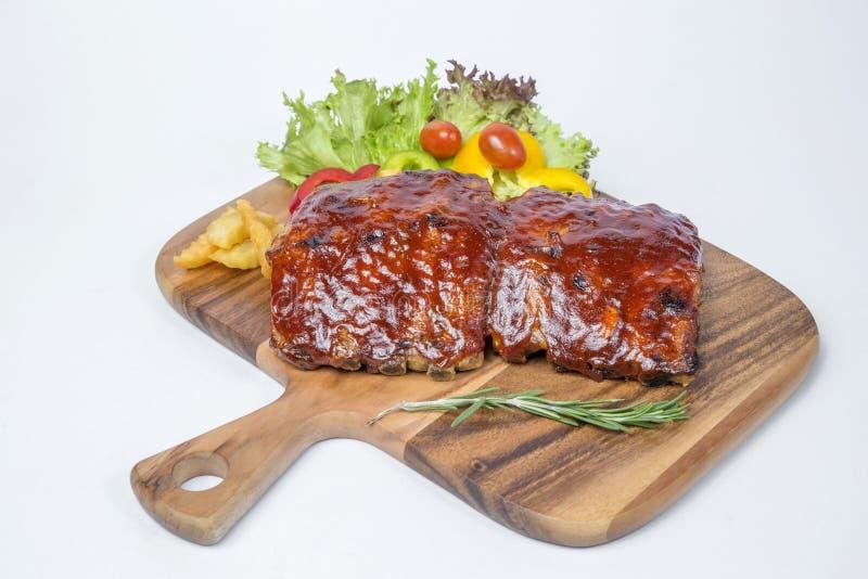 Σχάρα πλευρών χοιρινού κρέατος που εξυπηρετούνται με τη σαλάτα και γαλλικά που τηγανίζεται στοκ εικόνες με δικαίωμα ελεύθερης χρήσης