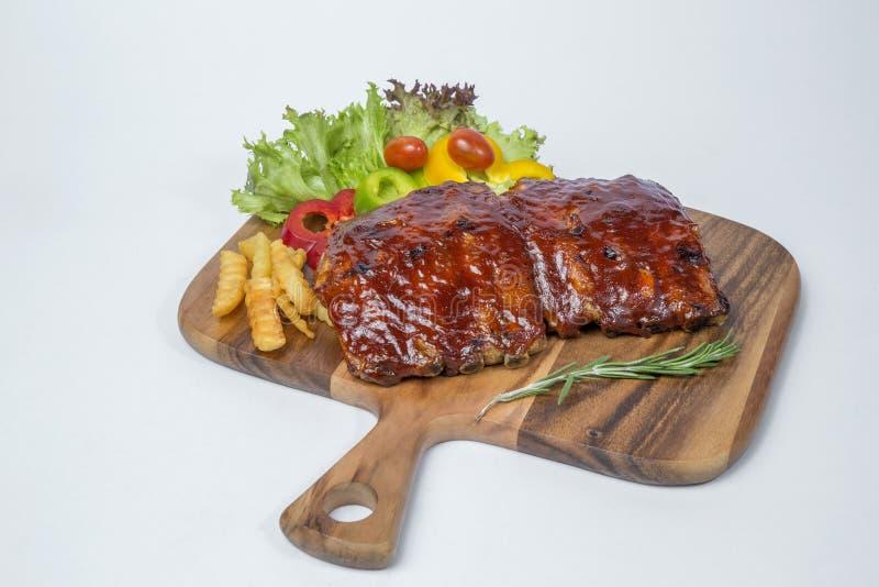Σχάρα πλευρών χοιρινού κρέατος που εξυπηρετούνται με τη φρέσκια σαλάτα και γαλλικά που τηγανίζεται στοκ φωτογραφία με δικαίωμα ελεύθερης χρήσης
