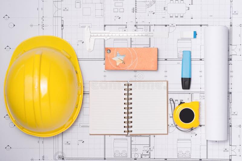 Σχέδια κατασκευής με τα εργαλεία κρανών και σχεδίων στα σχεδιαγράμματα στοκ φωτογραφία