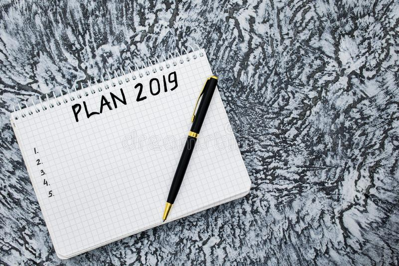 Σχέδιο για το 2019, σημειωματάριο και μάνδρα σε ένα κατασκευασμένο γκρίζο υπόβαθρο στοκ εικόνα