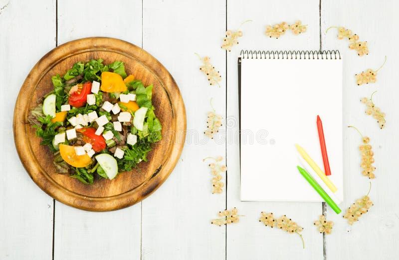 Σχέδιο διατροφής - μια σαλάτα των φρέσκων λαχανικών και ενός κενού σημειωματάριου επάνω στοκ εικόνα