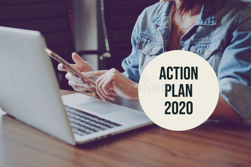 Σχέδιο δράσης 2020 με νέα ανεξάρτητη γυναίκα που χρησιμοποιεί smartphone και φορητό υπολογιστή σε σύγχρονο χώρο εργασίας, ανάλυση στοκ εικόνα με δικαίωμα ελεύθερης χρήσης