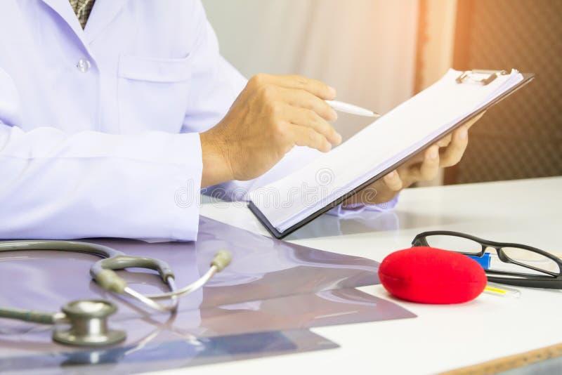 Σχέδιο θεραπείας του καρκίνου εκθέσεων γραψίματος μανδρών εκμετάλλευσης γιατρών για το γραφείο με το φως ηλιοβασιλέματος στοκ εικόνες με δικαίωμα ελεύθερης χρήσης