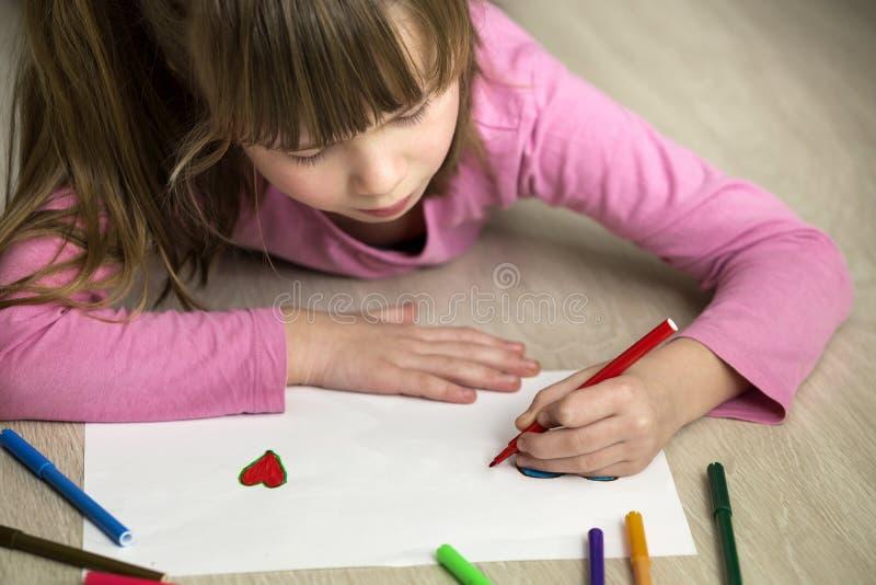 Σχέδιο κοριτσιών παιδιών με τη ζωηρόχρωμη καρδιά κραγιονιών μολυβιών στη Λευκή Βίβλο Αισθητική αγωγή, έννοια δημιουργικότητας στοκ εικόνες