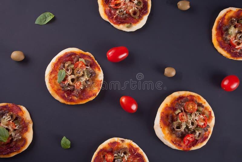 Σχέδιο με τη σπιτική μίνι πίτσα, τις ντομάτες κερασιών και τις πράσινες ελιές στο μαύρο υπόβαθρο στοκ εικόνες