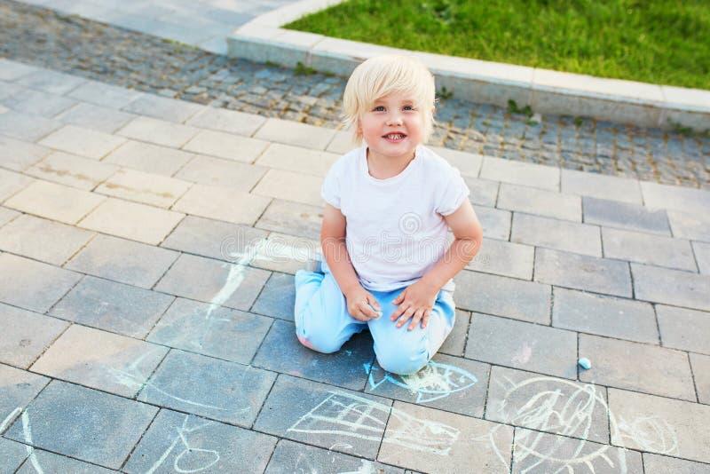 Σχέδιο μικρών παιδιών με τις κιμωλίες στην άσφαλτο στοκ εικόνα