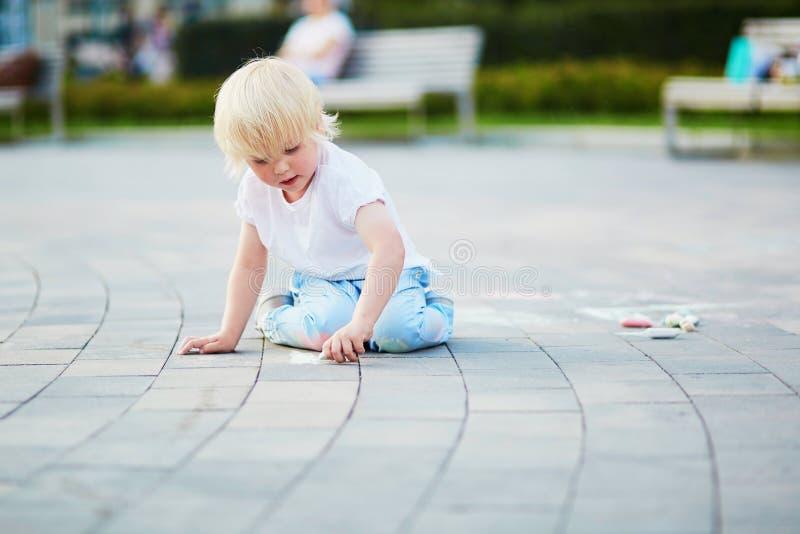 Σχέδιο μικρών παιδιών με τις κιμωλίες στην άσφαλτο στοκ εικόνες