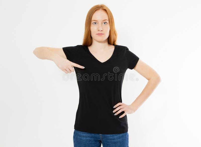 Σχέδιο μπλουζών, ευτυχής έννοια ανθρώπων - χαμογελώντας κόκκινη γυναίκα τρίχας στην κενή μαύρη μπλούζα που δείχνει τα δάχτυλά της στοκ φωτογραφίες