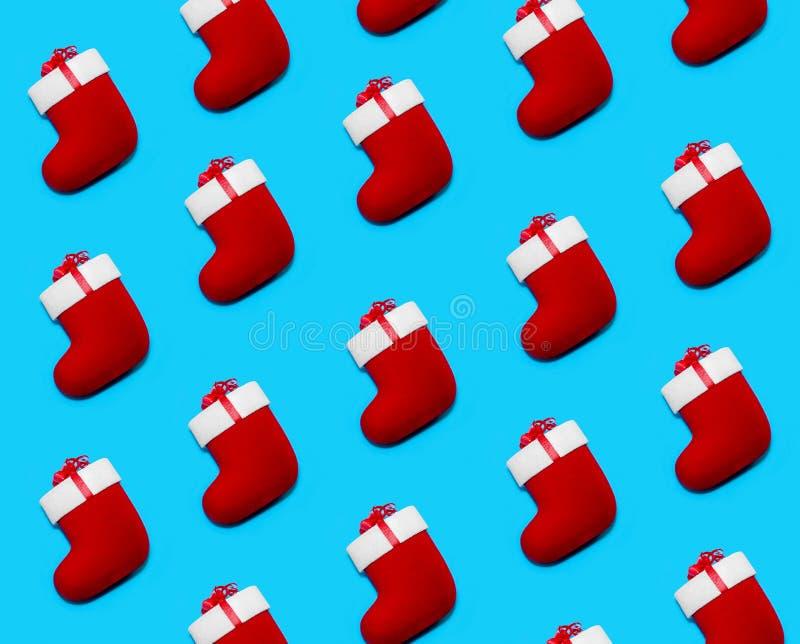 Σχέδιο που γίνεται με τις κόκκινες κάλτσες Χριστουγέννων στο μπλε υπόβαθρο Δημιουργική ελάχιστη σύνθεση διακοπών Επίπεδος βάλτε στοκ εικόνες