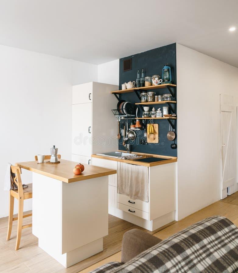 Σχέδιο της σύγχρονης εγχώριας κουζίνας στο αττικό και αγροτικό ύφος Μαύρος τοίχος με τα ράφια, δίσκοι, βάζα, κούπες Ψυγείο, που δ στοκ εικόνες